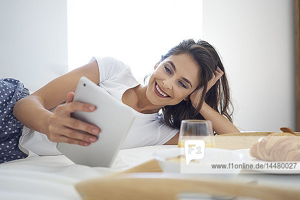 Young woman having breakfast in bed  using digital tablet  reading