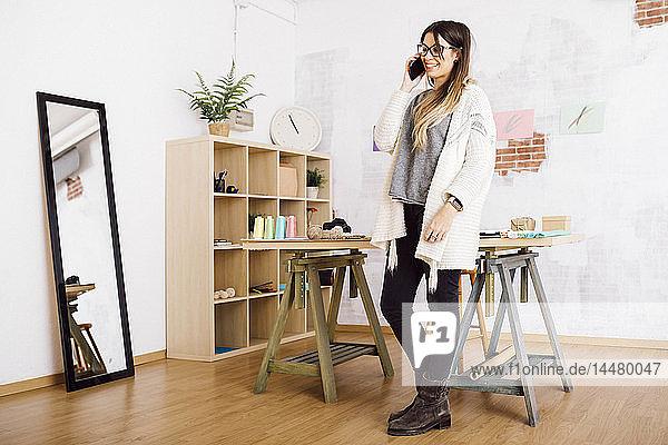 Lächelnde junge Frau telefoniert in ihrem Atelier