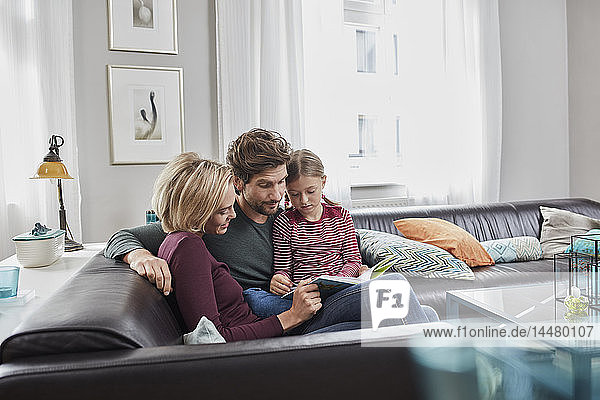 Family sitting on couch at home reading book together