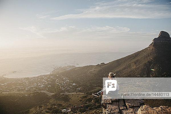 Südafrika  Kapstadt  Kloof Nek  Frau sitzt bei Sonnenuntergang auf einem Felsen