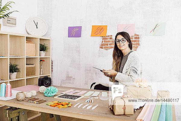 Junge Frau bastelt zu Hause  sitzt mit Tablett am Schreibtisch