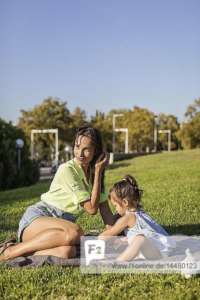Glückliche Mutter spielt mit Tochter auf einer Decke im Park