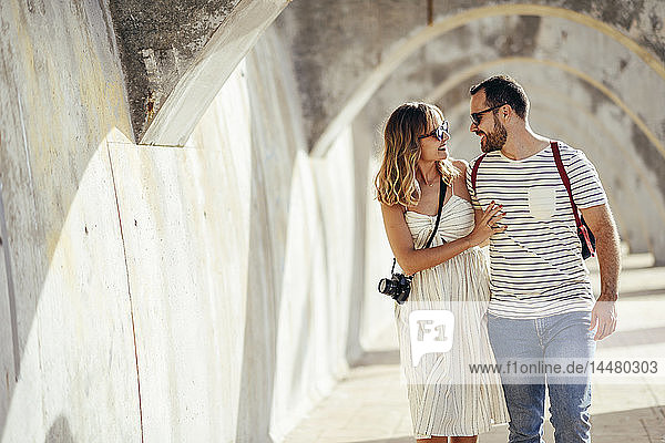 Spain  Andalusia  Malaga  happy tourist couple walking under an archway in the city