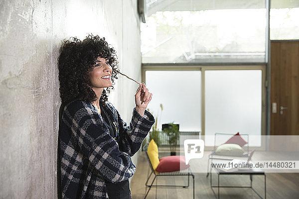 Lächelnde Frau lehnt an Betonwand in einem Loft