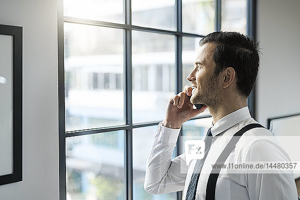 Smiling businessman looking out of window in office talking on cell phone