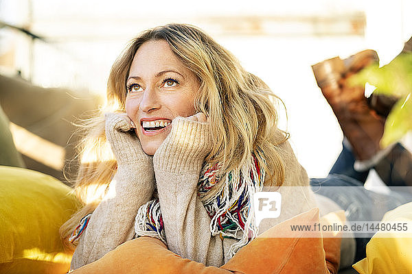 Portrait of smiling blond mature woman relaxing in winter garden