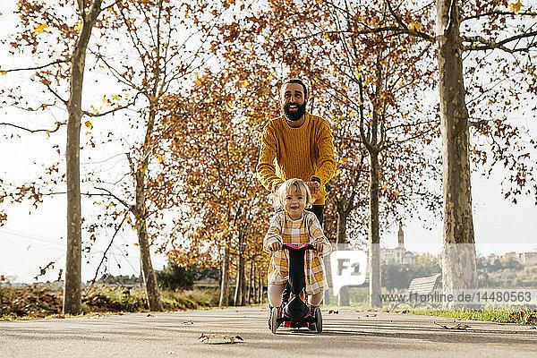 Vater und Tochter genießen im Herbst einen Vormittag im Park  Mädchen auf dem Roller