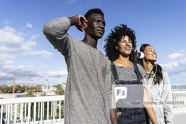 Friends standing on a bridge  having fun  listening music