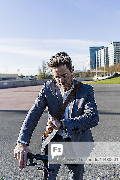 Mature businessman commuting in the city with his kick scooter  checking the time