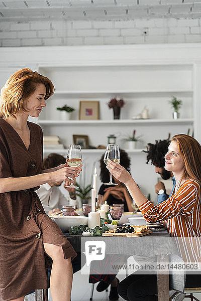 Freunde trinken Wein bei einer Dinnerparty  klirrende Gläser