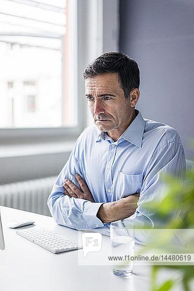 Seriöser Geschäftsmann am Schreibtisch sitzend im Büro