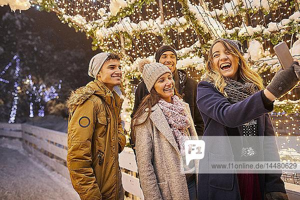Vier Freunde beim Selfie auf der Eisbahn
