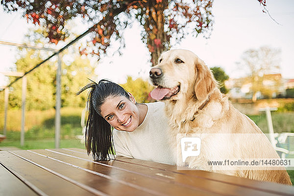 Portrait of happy young woman with her Golden retriever dog resting in a park