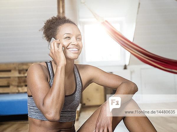 Glückliche junge Frau in Sportkleidung am Handy