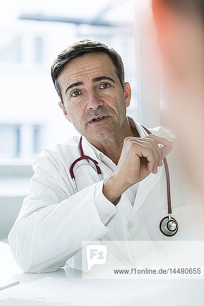 Porträt eines Arztes im Gespräch mit einem Patienten in der medizinischen Praxis