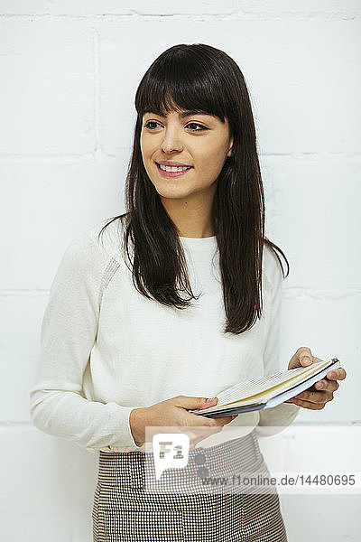 Portrait of smiling young woman with notebook at brick wall