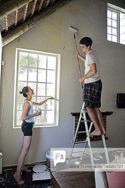Young couple renovating their home painting the wall together