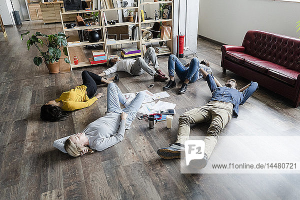 Business team lying on the floor surrounded by documents in loft office