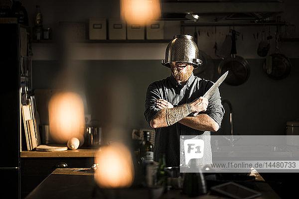 Mann mit Küchenmesser in der Küche stehend  Sieb als Helm tragend