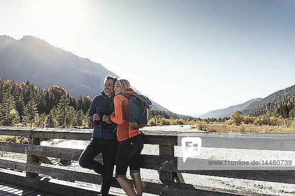 Österreich  Alpen  glückliches Paar auf einer Wanderung auf einer Brücke stehend