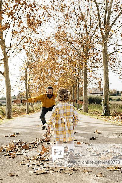 Vater und Tochter genießen im Herbst einen Vormittag im Park
