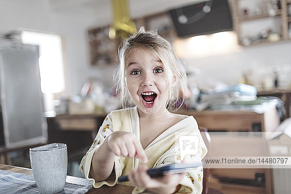 Portrait of excited little girl in the kitchen pointing at smartphone