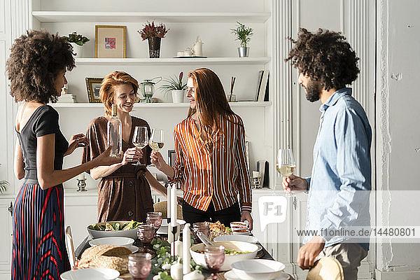 Freunde  die bei einer Dinnerparty Wein trinken und anstoßen