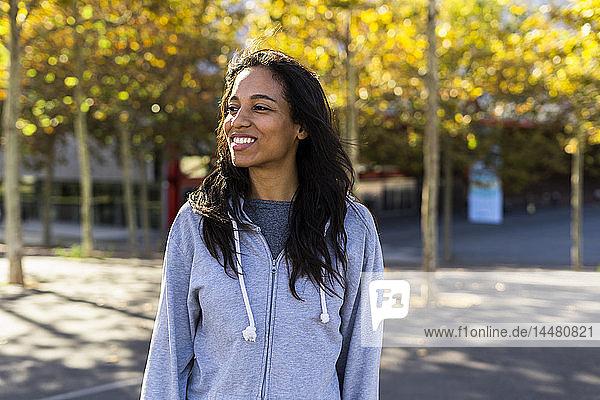 Porträt einer lächelnden Frau  stehend in einem Park