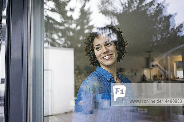 Porträt einer lächelnden Frau zu Hause  die aus dem Fenster schaut