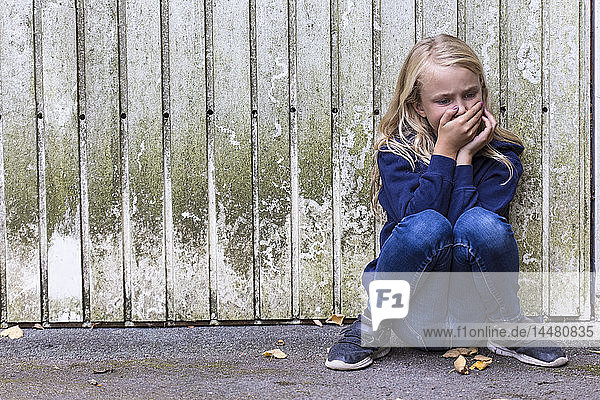Frightened girl crouching in front of wooden wall