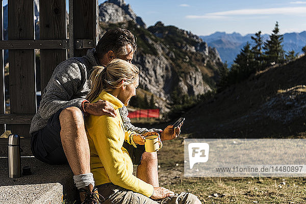 Hiking couple sitting in front of mountain hut  taking a break  looking at smartphone