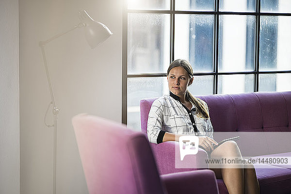 Young businesswoman sitting on violet couch with tablet