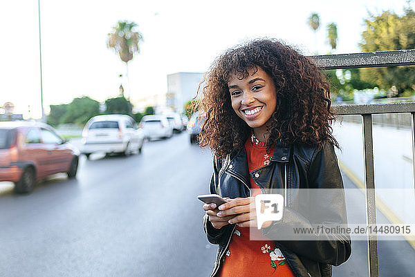 Portrait of smiling young woman with smartphone standing at roadside
