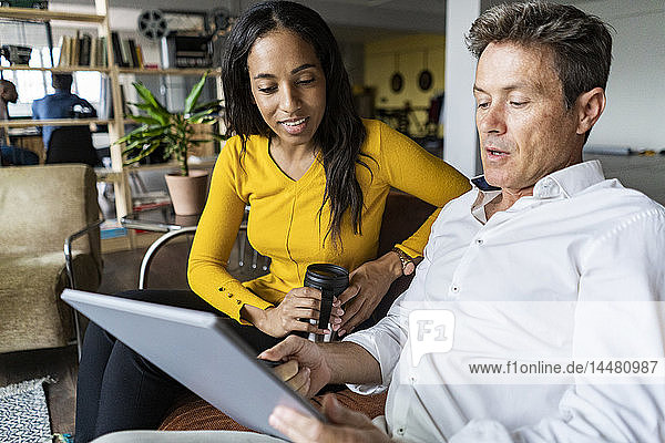 Businesswoman and businessman sharing tablet on sofa in loft office