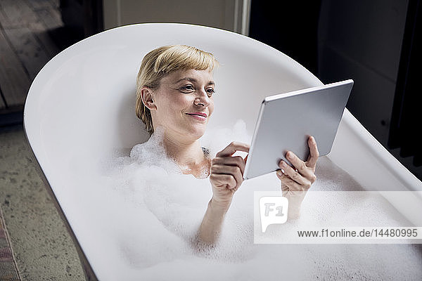 Portrait of relaxed woman taking bubble bath while using tablet