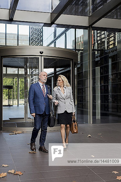 Senior businessman and businesswoman walking and talking in a foyer