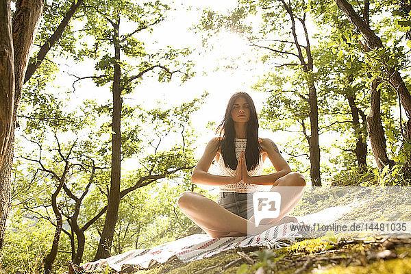 Junge Frau sitzt auf einer Decke im Wald und praktiziert Yoga
