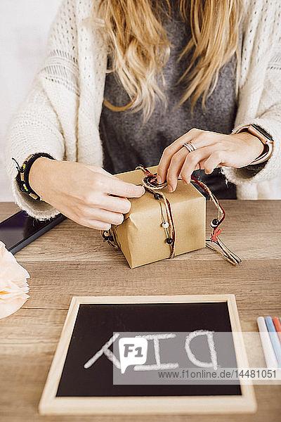 Junge Frau packt in ihrem Atelier ein Geschenk ein