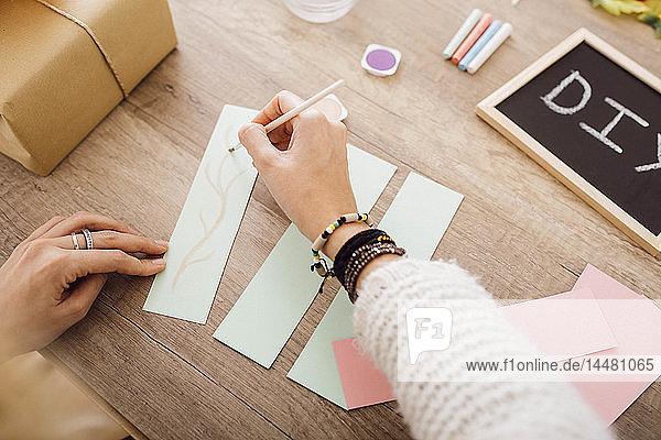 Junge Frau bastelt in ihrem Atelier mit Aquarellfarben
