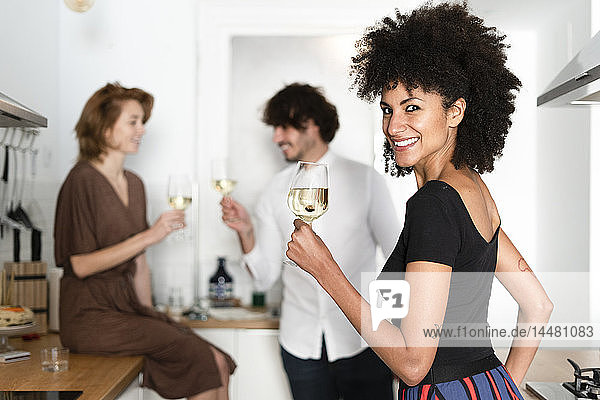 Friends having fun at a party  drinking wine in the kitchen