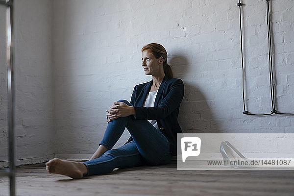 Barfüßige Geschäftsfrau sitzt im Büro auf dem Boden