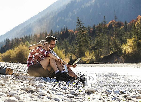 Österreich,  Alpen,  Ehepaar auf Wanderung mit Pause an einem Bach beim Kartenlesen