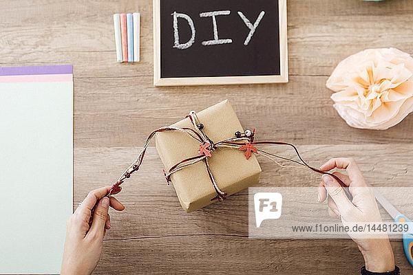 Draufsicht einer jungen Frau  die in ihrem Atelier ein Geschenk einpackt