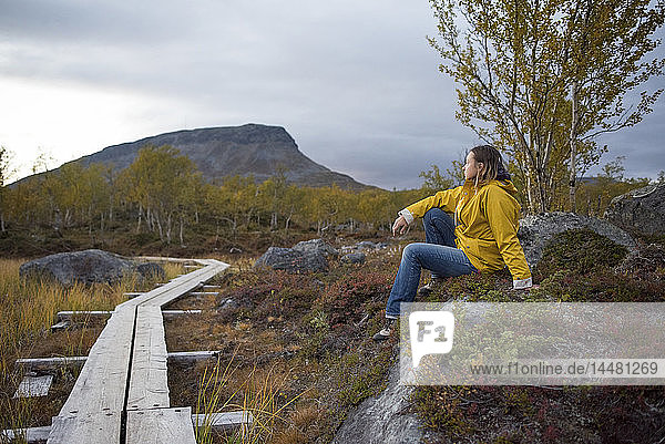 Finnland  Lappland  Kilpisjaervi  Frau an Holzpromenade sitzend