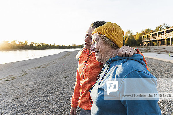 Fit grandmother and granddaughter walking at the river with arms around  having fun