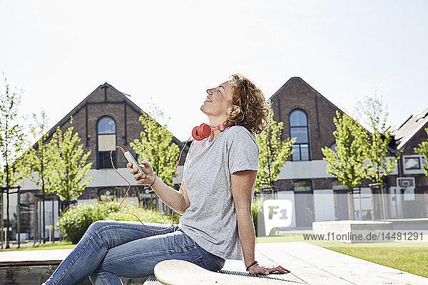 Lächelnde junge Frau mit Kopfhörern  Longboard und Smartphone in städtischer Umgebung