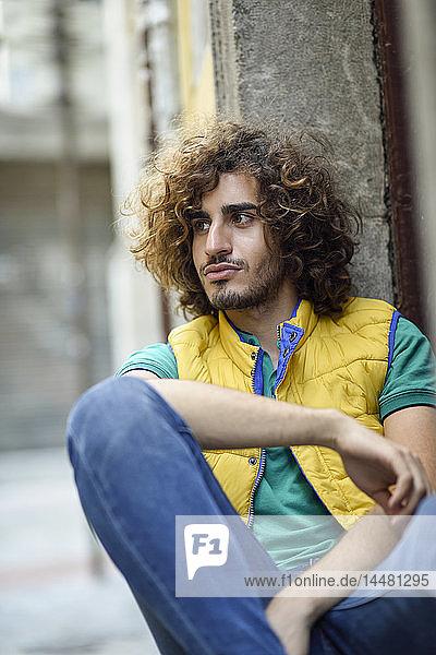 Porträt eines jungen Mannes mit Bart und lockigem Haar mit gelber Weste  der etwas beobachtet