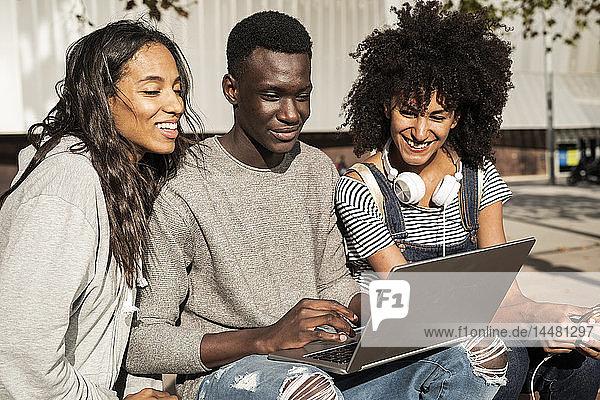 Freunde sitzen auf einer Bank in der Stadt  amüsieren sich  benutzen einen Laptop