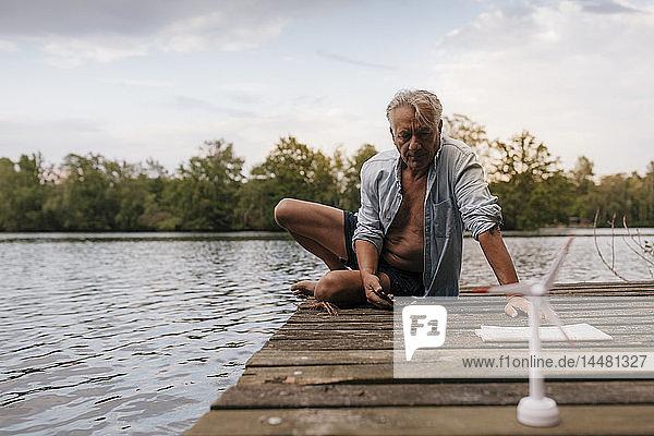 Älterer Mann sitzt auf einem Steg an einem See mit einem Modell einer kleinen Windkraftanlage