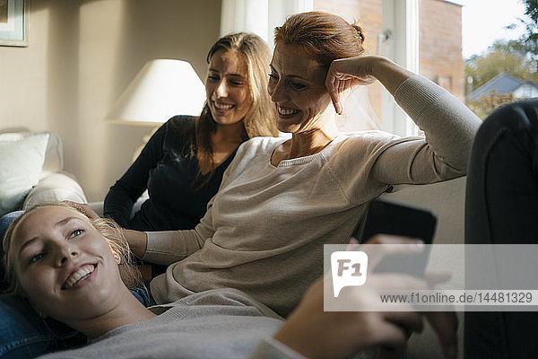 Glückliche Mutter mit zwei Teenager-Mädchen auf der Couch zu Hause mit Handy